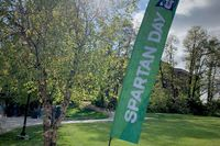 A flag is posted in the ground beside a tree. It reads Spartan Day and features the Spartan logo