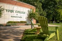 A large sign shows the York College of Pennsylvania logo on a brick wall as two green Adirondack chairs sit in the foreground on an autumn day in the campus quad