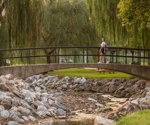 a student crosses the bridge at Tyler Run